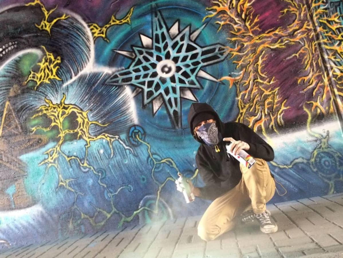 Graffitimaalari graffitin edessä Hakametsän alikulkutunnelissa Tampereella