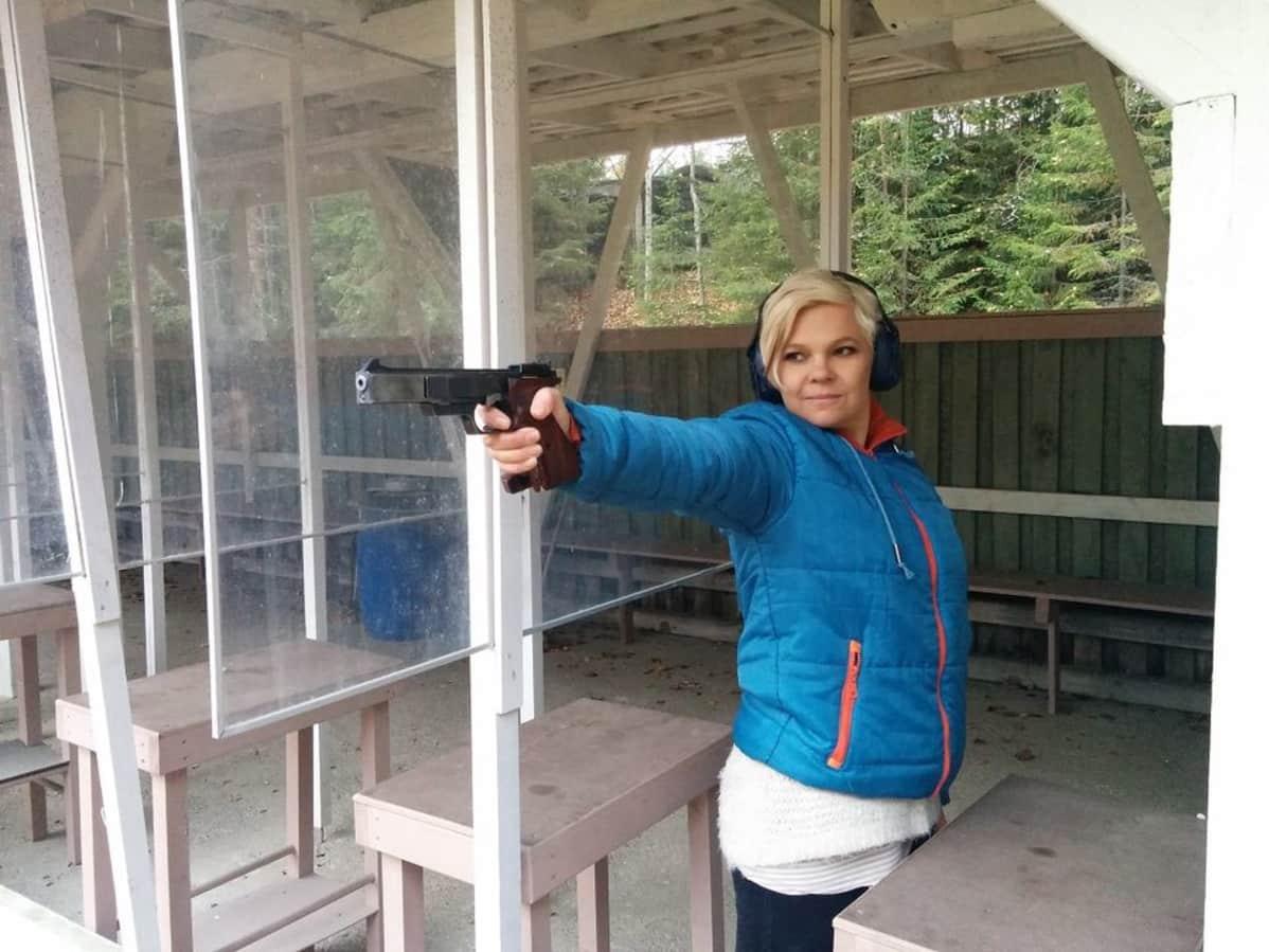 Naisampuja tähtää pienoispistoolilla ampumaradalla.