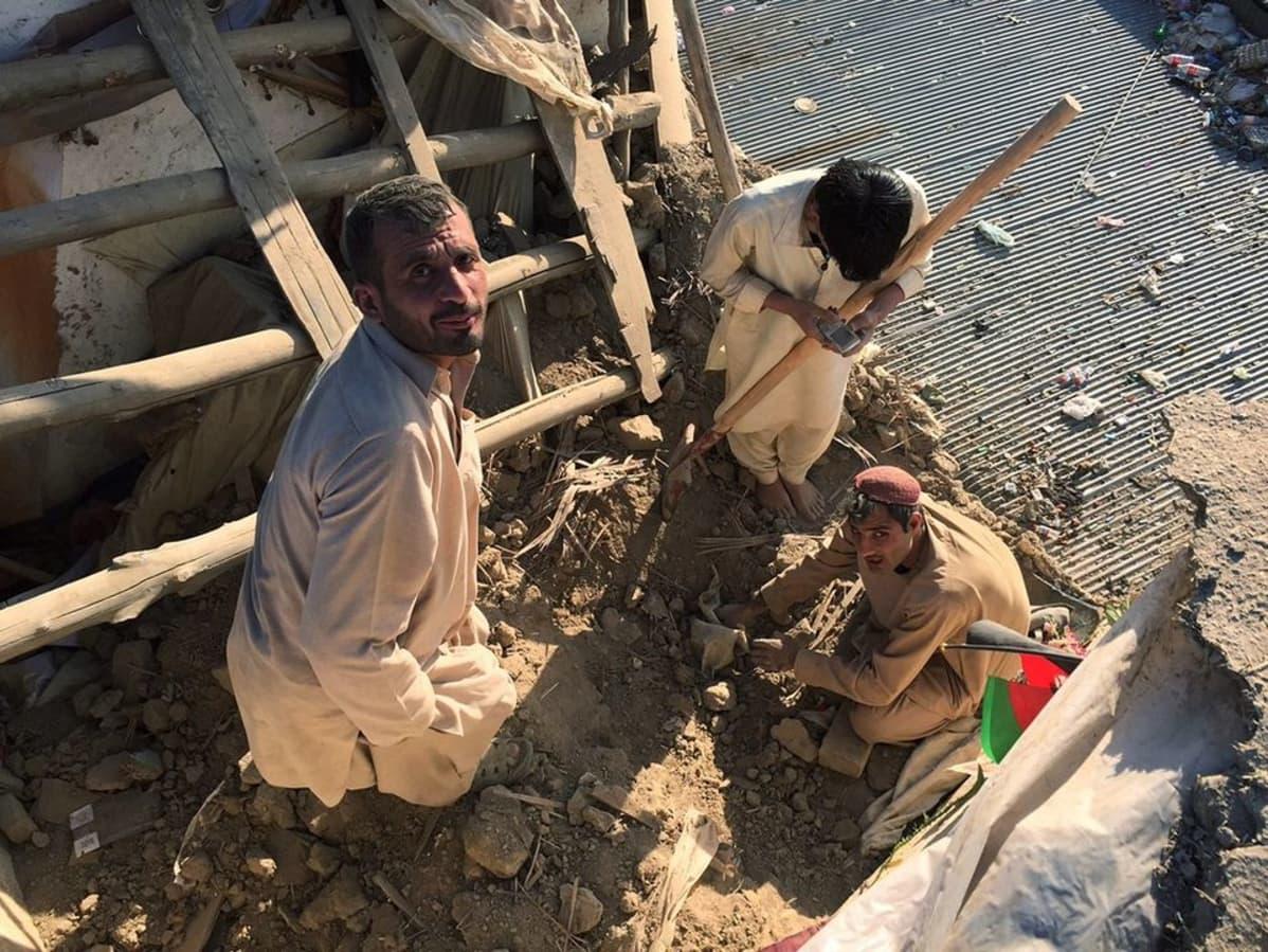 Kolme miestä romahtanutta rakennusta tutkimassa. Yhdellä on lapio, toinen kaivaa maata käsin.