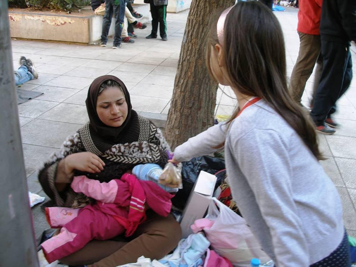 Kreikkalaistyttö jakaa pakolaislapsille itse tekemiään keksejä.