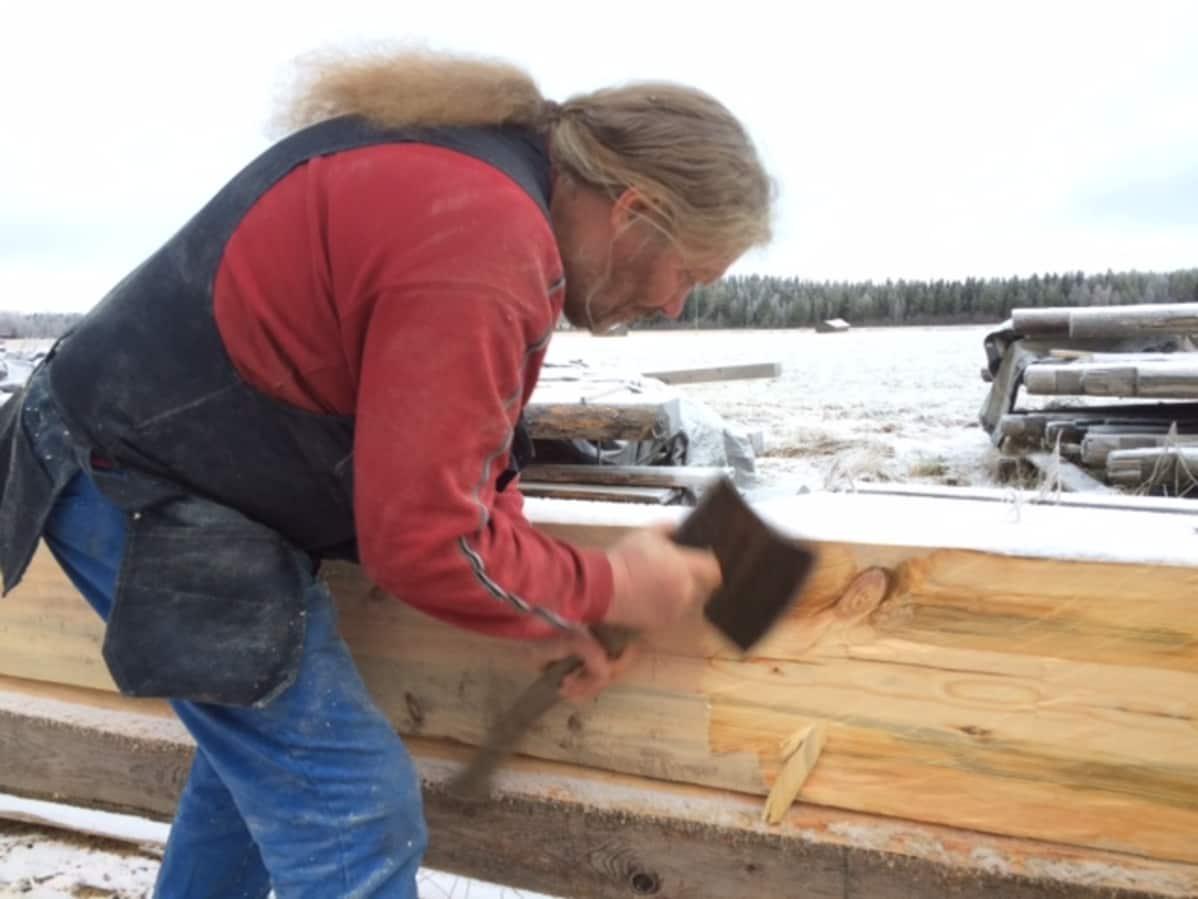 Seppo Kalliokoski siistii hirren pintaa piilukirveellä.