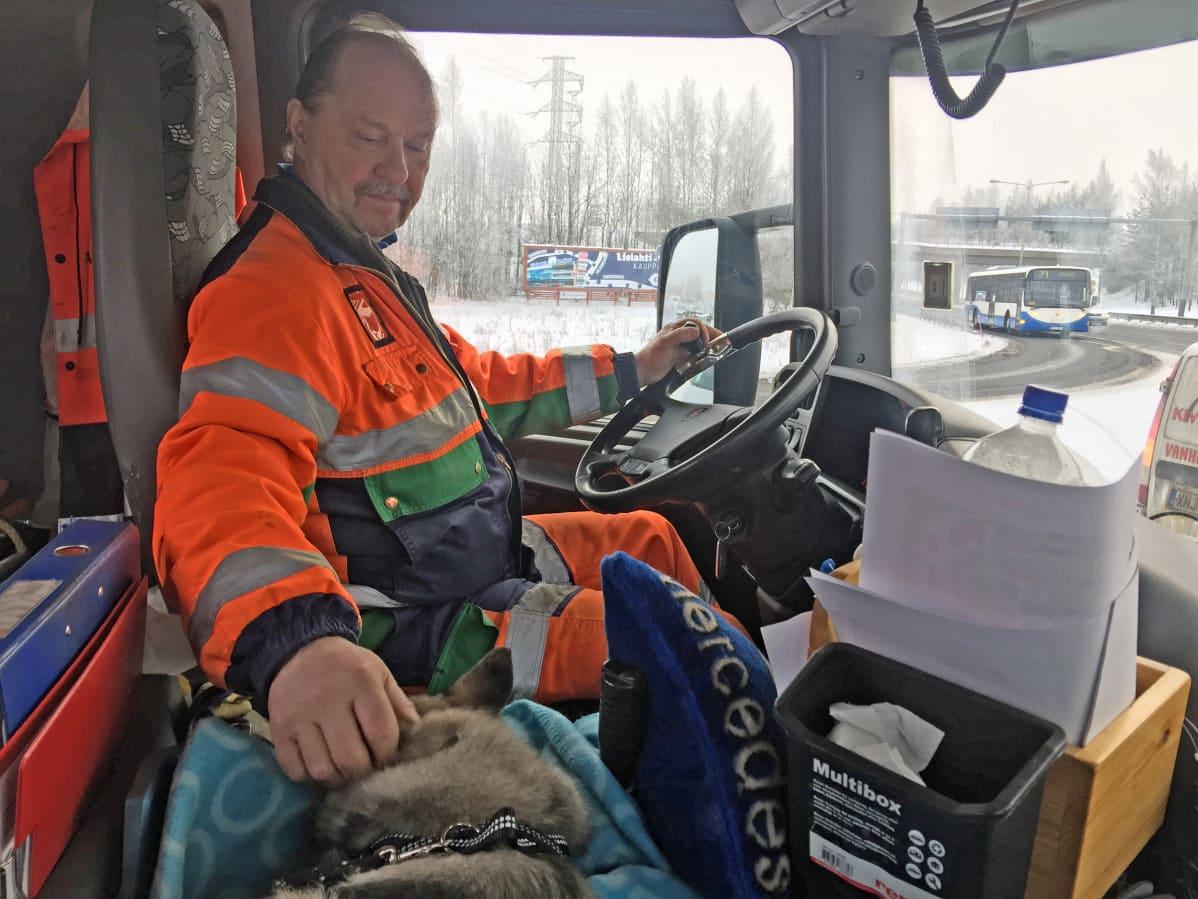 Arto Paltta rapsuttaa pientä koiraa kuorma-auton kyydissä
