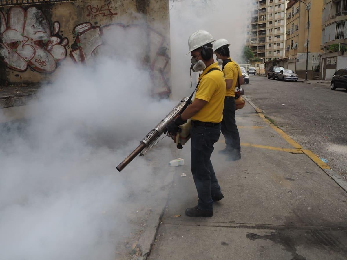 Keltaisiin paitoihin pukeutuneet, valkokypäräiset miehet ruiskuttavat hyttymyrkkyä kadulla.