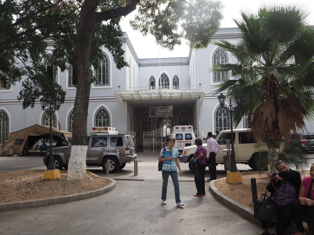 Yleiskuva sairaalasta, pihalla ihmisiä, autoja ja puita sekä palmu.