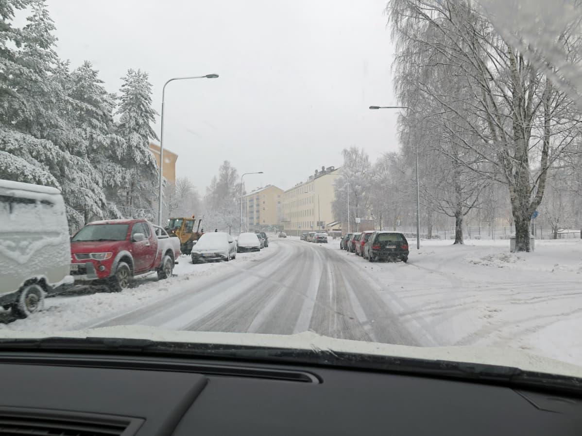 Luminen tie, jonka varrelle on pysäköity autoja