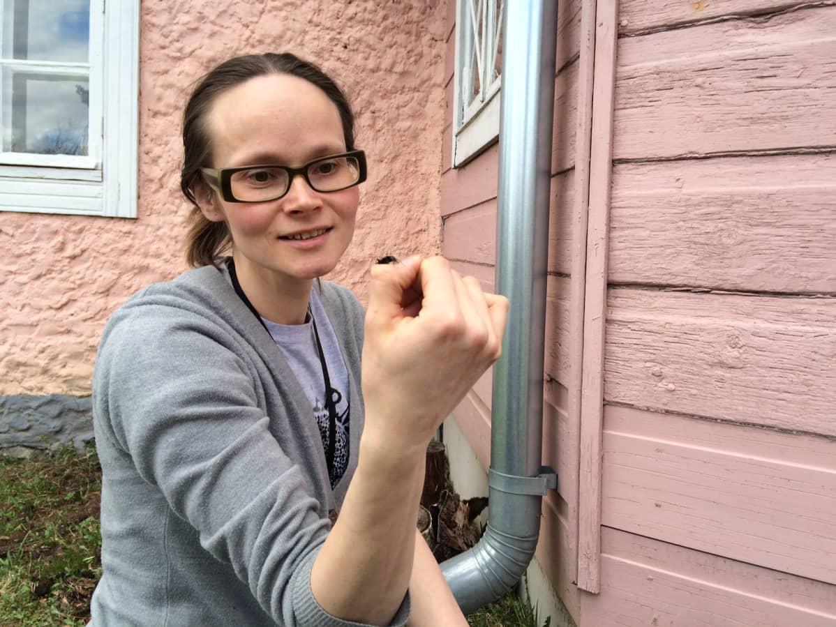 Urpolan luontokeskuksen toiminnanohjaaja Kerttu Hakala tarkastelee käsivarrelleen lennähtänyttä kuoriaista. Takana luontokeskus, joka toimii Mikkelin vanhimmassa, vuonna 1782 rakennetussa asuinrakennuksessa.