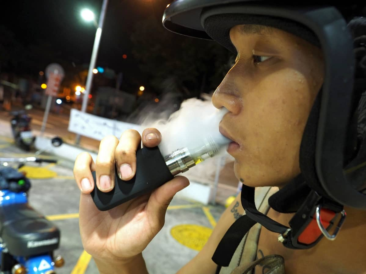 epa04916328 A man smokes an electronic cigarette in Taipei, Taiwan, 06 September 2015. Taiwanese can buy e-cigarettes from shops who advertise e-cigarettes on-line. The e-cigarettes are made in China, the Philippines and the United States, a shop owner said. Taiwan's anti-smoking group John Tong Foundation is urging the government to ban the sale of e-cigarettes because e-cigarettes cannot help people quit smoking. The foundaiton clams that e-cigarette is harmful to health as its vapour contains nicotine, toxicants, carcinoge and heavy metal. And as its vapour smells sweet, many young people are addicted to e-cigarette, believing it is not cigarette and it is safe.  EPA/DAVID CHANG