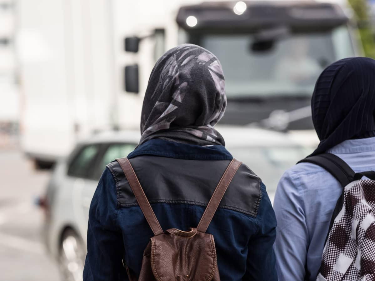 Kaksi huivipäistä naista odottaa pääsevänsä tien yli.