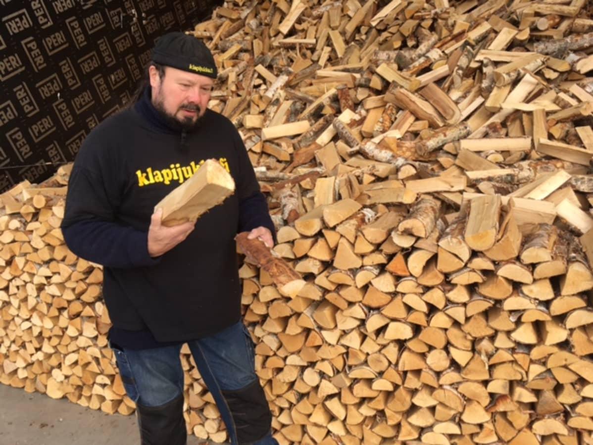 Yrittäjä Jukka Virtanen seisoo klapinon ja -kasan edessä ja pitelee kahta puuta käsissään.