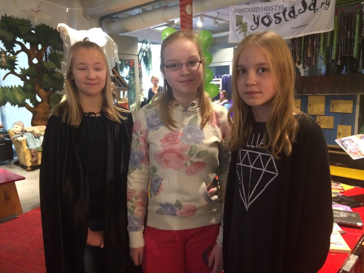 Kolme tyttöä katsoo kameraa lasten tapahtumassa Tampereella.