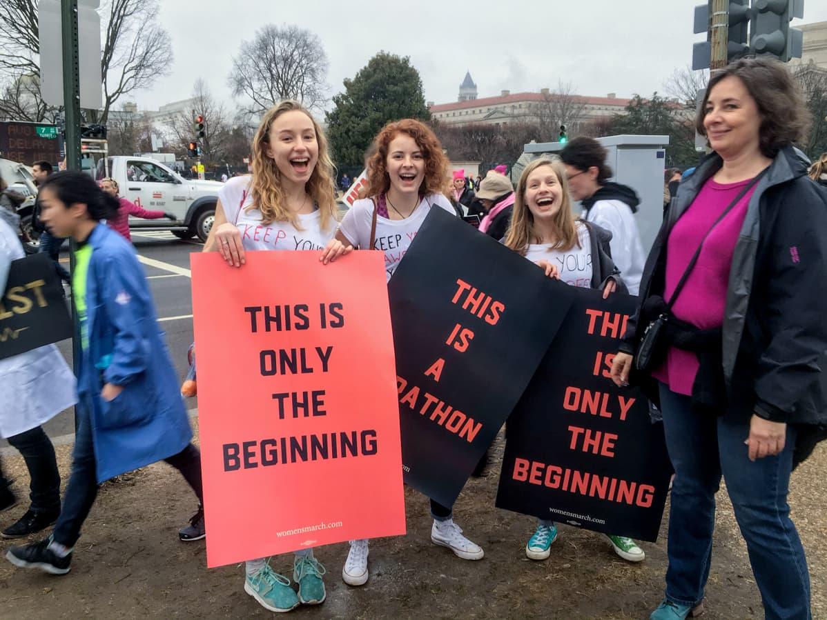 Kuvassa kolme teinityttöä ja Jennifer Heverly. Kyltit julistavat, että This is only the beginning
