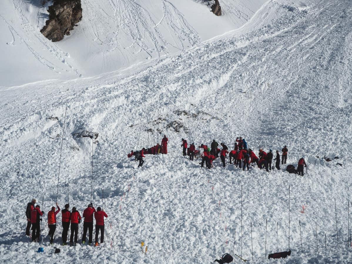Puna-asuisia ihmisiä lumisilla rinteillä.