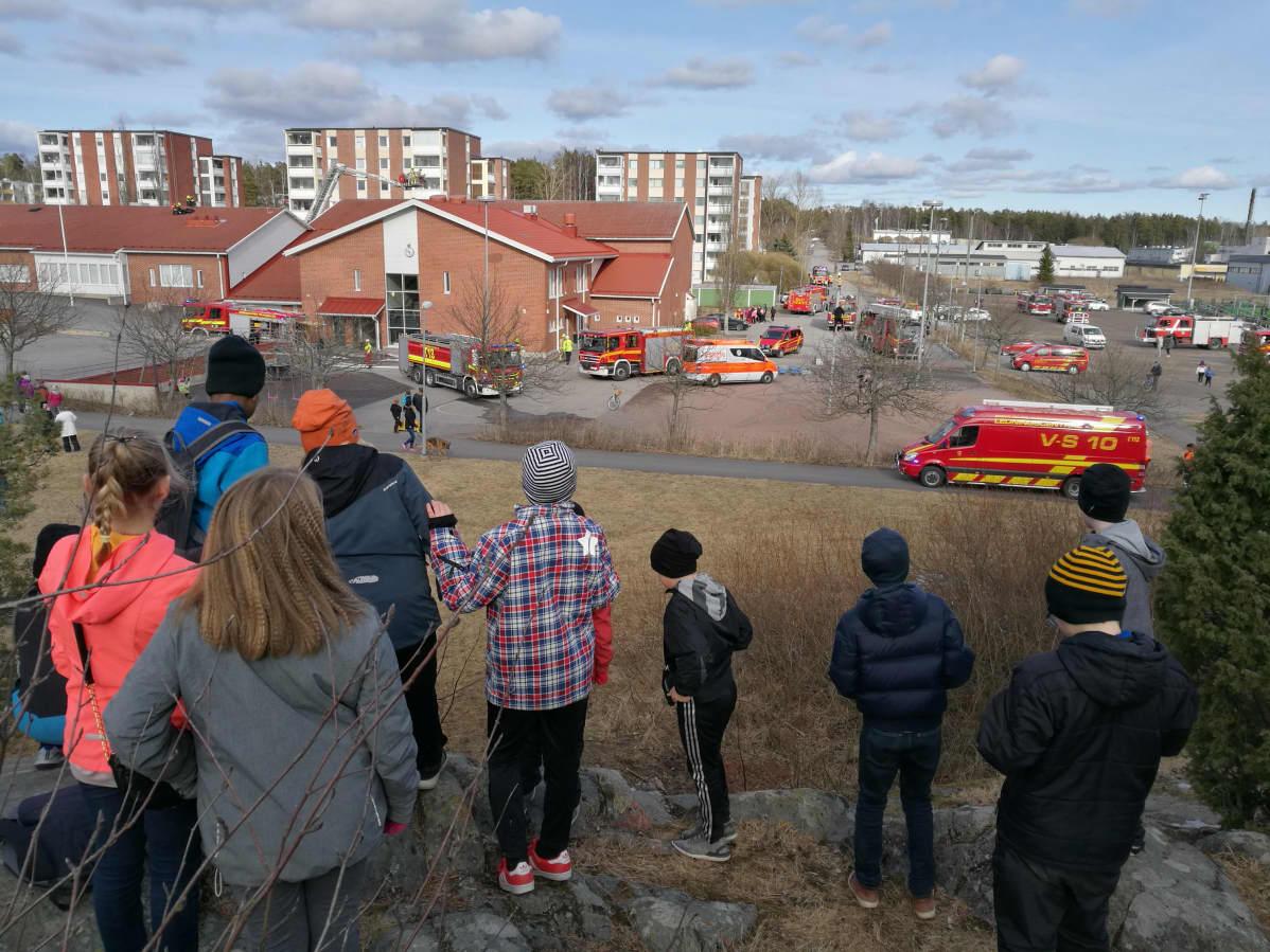Lapset katsovat kalliolla koulun pihalla olevia paloautoja ja -miehiä.