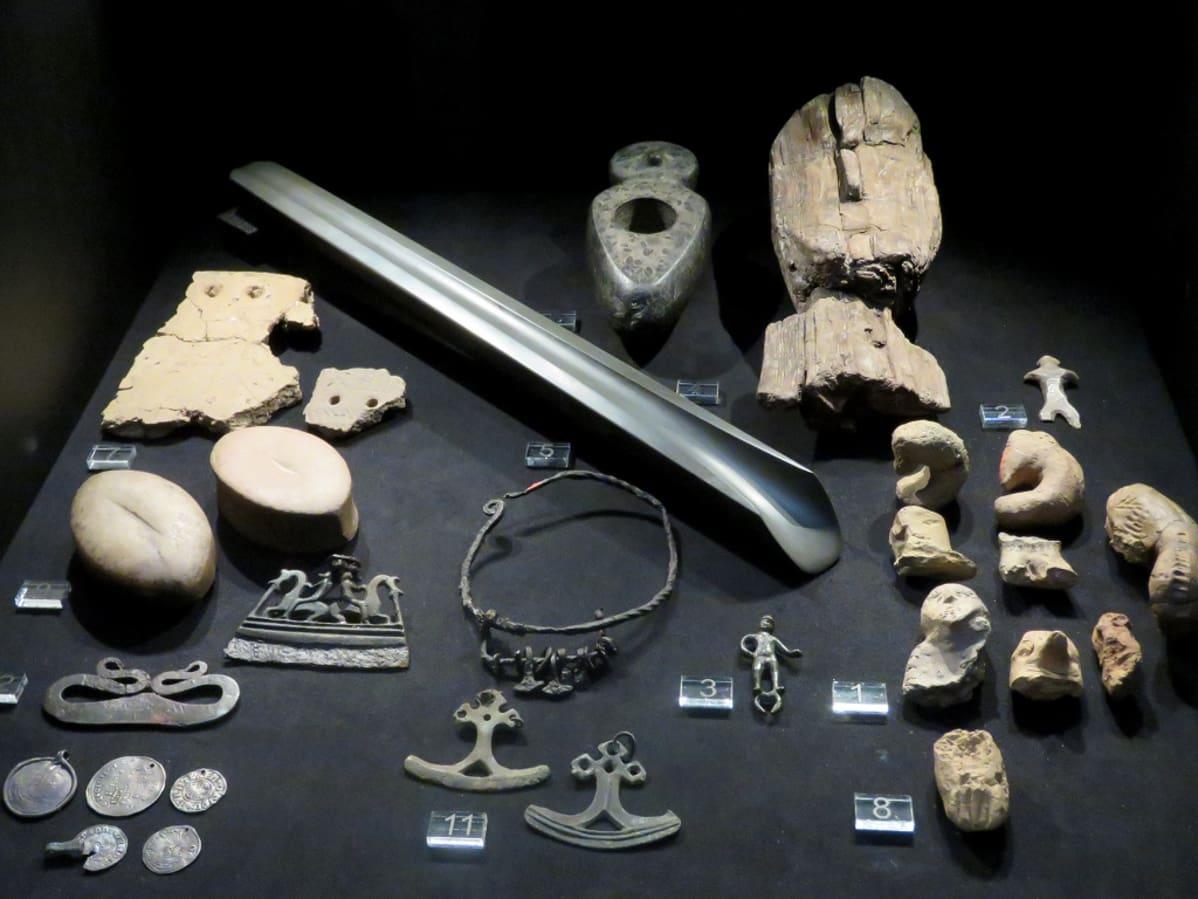Kivi- ja rautakautisia esineitä vitriinissä, muun muassa kolikoista tehtyjä riipuksia ja savisia ihmishahmoja.