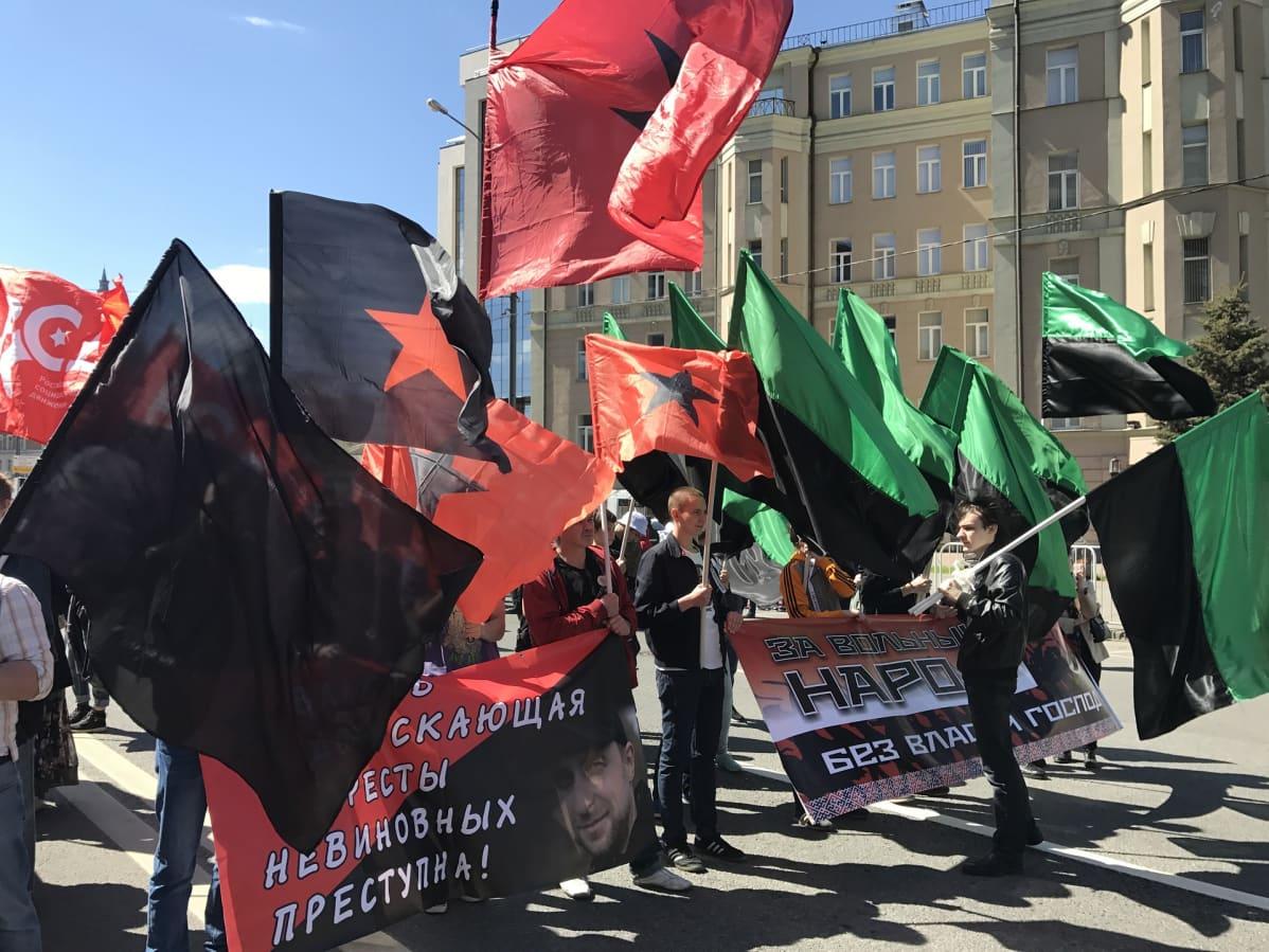Mustia ja punaisia tähtilippuja kantavia ihmisiä sekä mustavihreitä lippuja.