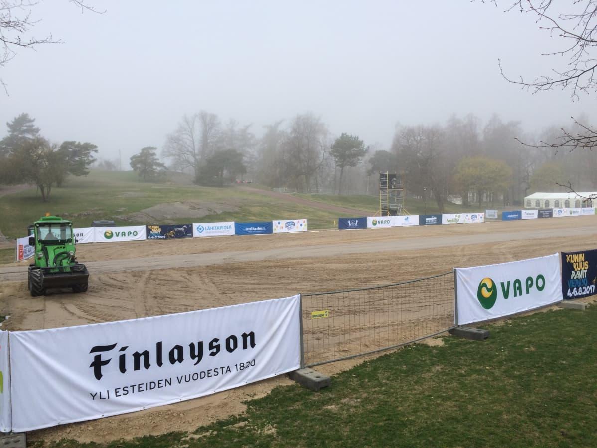 Traktori tasoittaa hiekkaa kentällä
