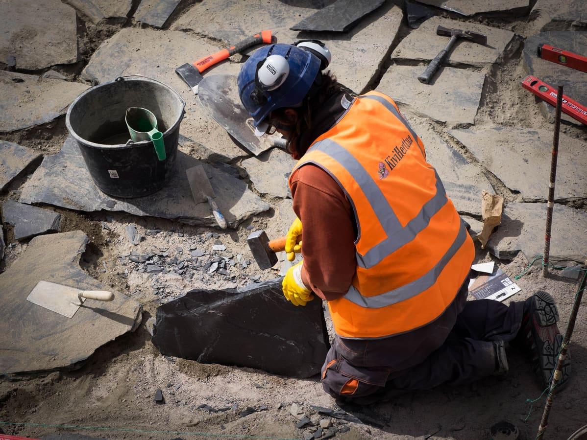 Rakennustyöläinen tekee kivilaatoitusta ulos.