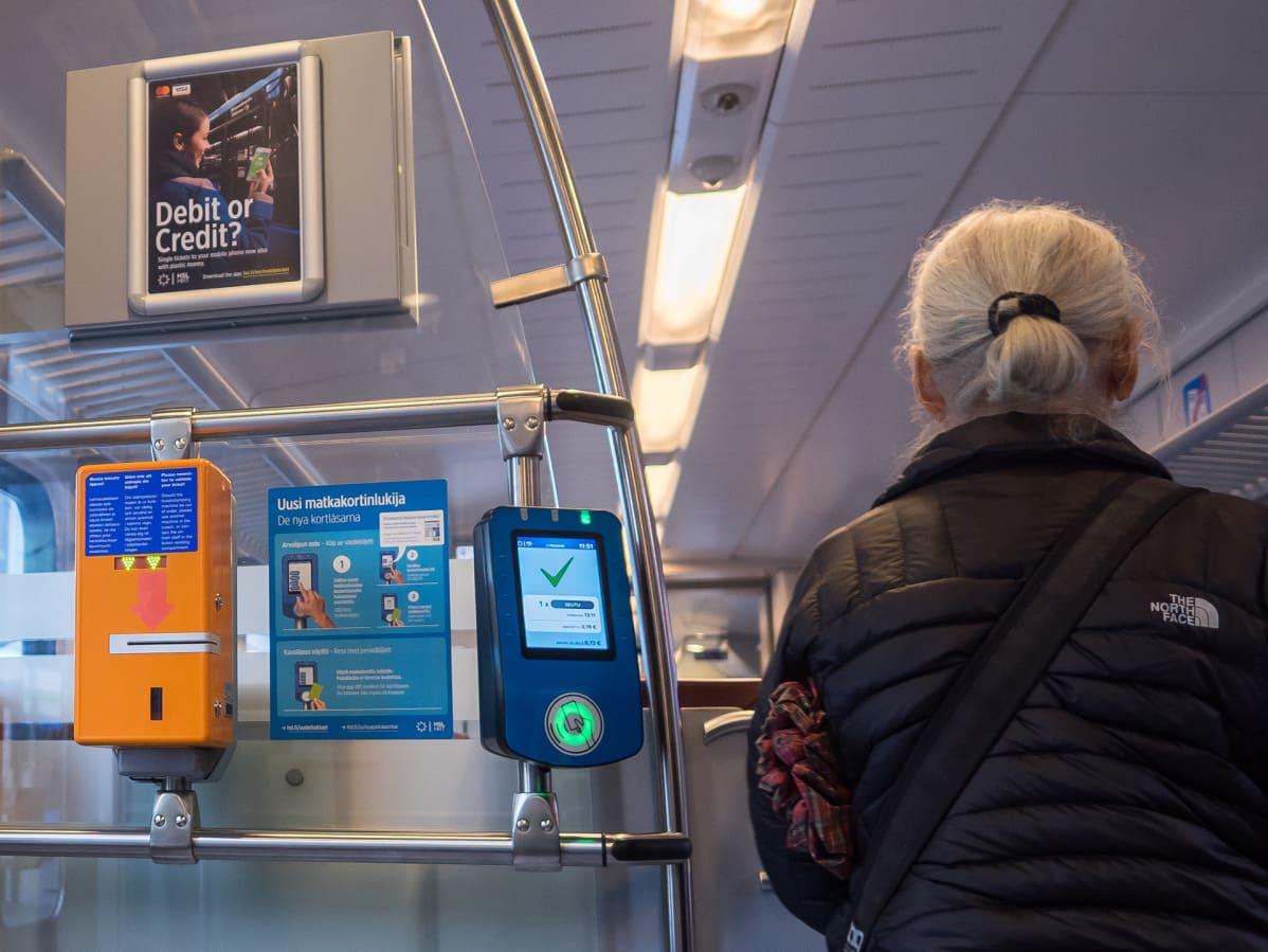 Nainen luki matkakorttinsa astuessaan junaan.