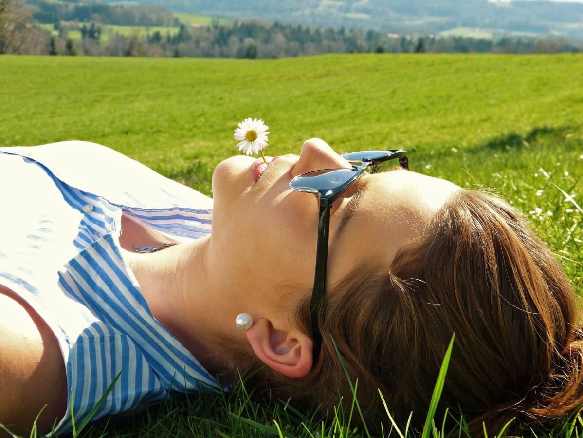 Tyttö makaa pellolla.