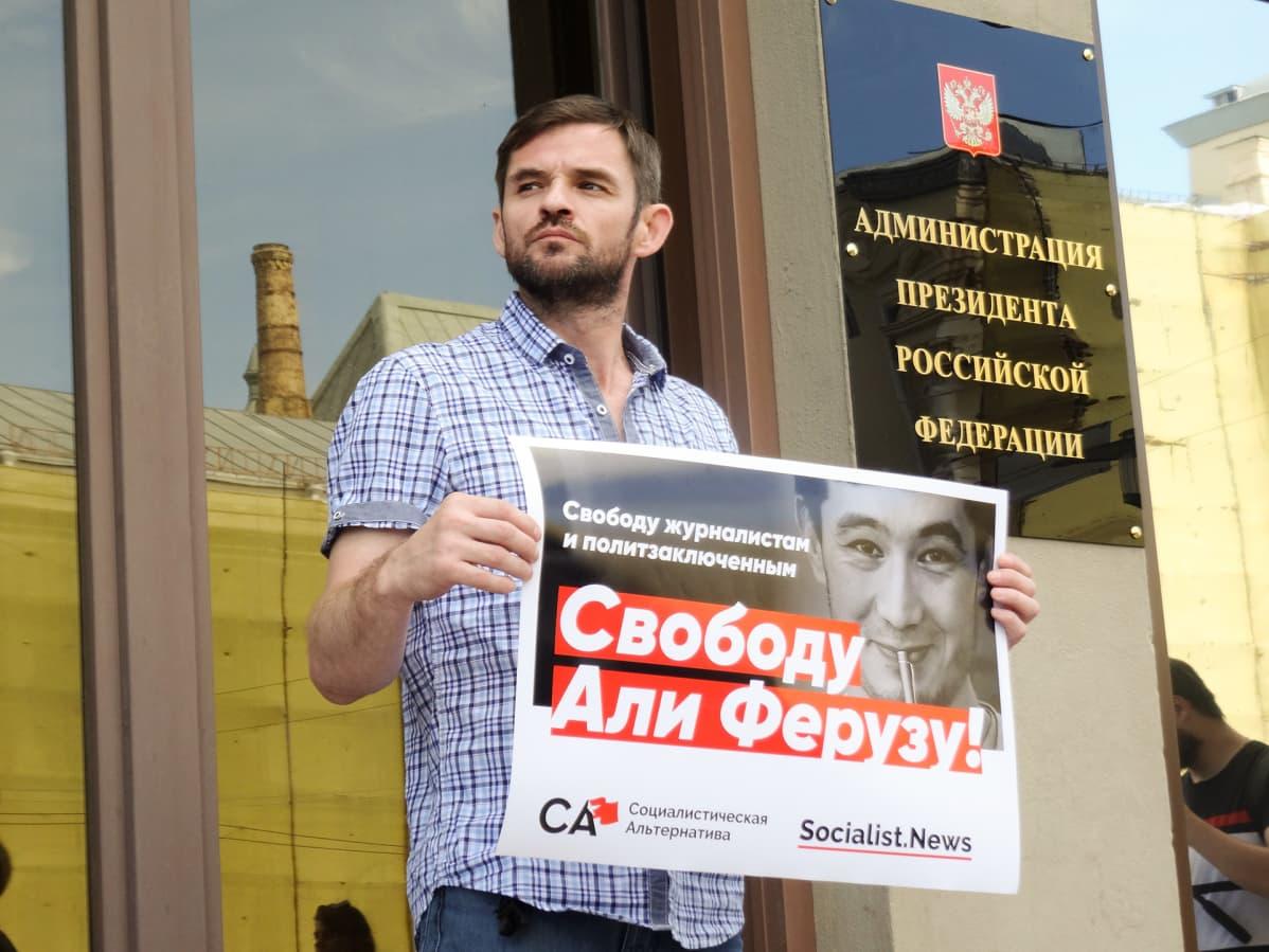 Jevgeni Pavlovski osoittaa mieltä Ali Feruzin puolesta presidentinhallinnon ovella.