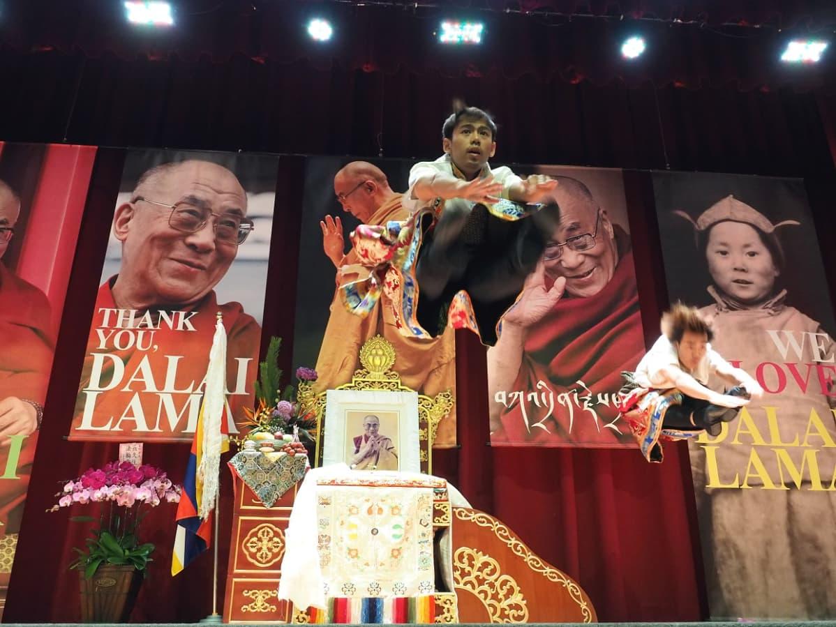 Taistalla Dalai laman kasvoja kirjojen kansissa. Edessä tanssija hyppää korkealle ilmaan.