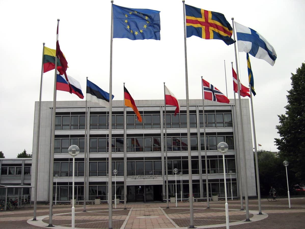 Liput liehuvat Ahvenanmaan itsehallintorakennuksen edessä.