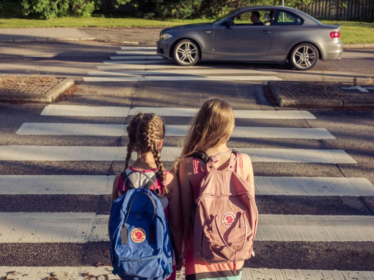 Koululaiset ylittävät tietä suojatiellä.