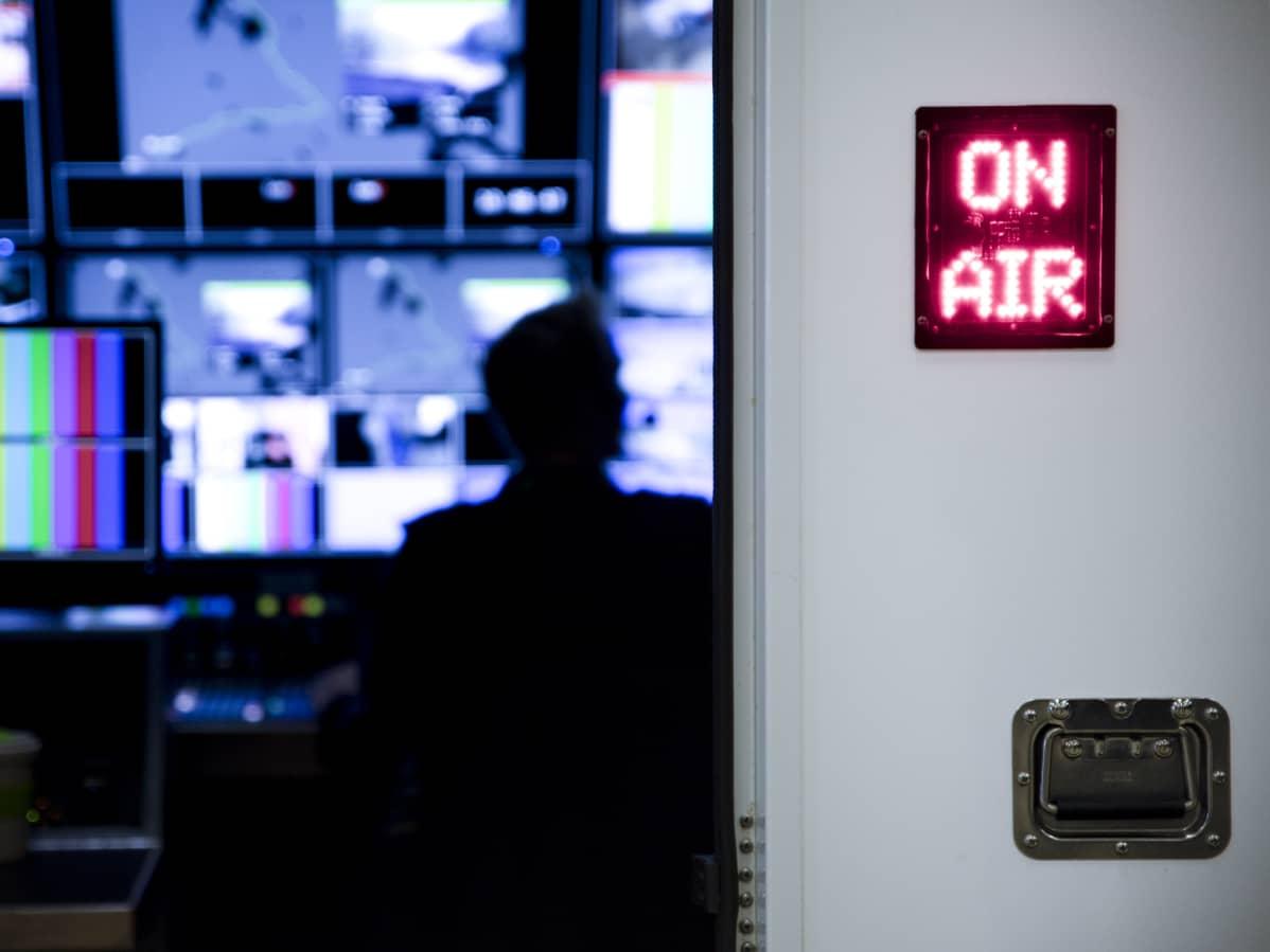 Kuvaruutuja tv-ohjaamossa, on air -kyltissä palaa valo.