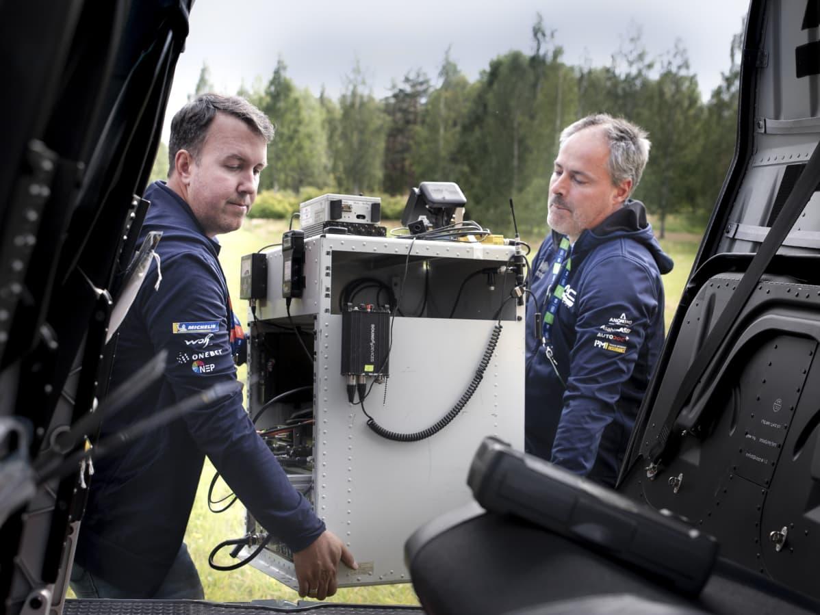 Clint Fast ja Bart Van Aert kantavat tv-lähetintä helikopteriin.