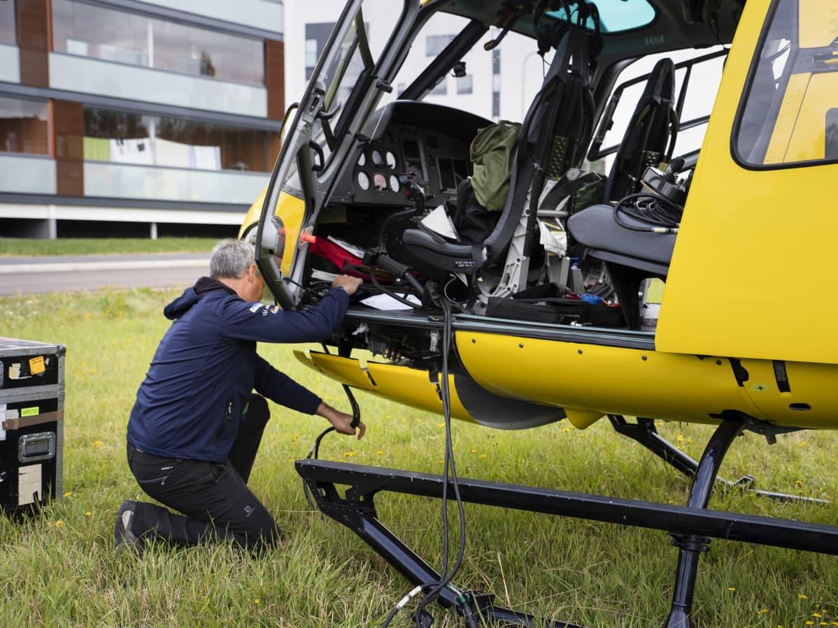 Bart Van Aert kiinnittää kuvauskalustoa helikopteriin.