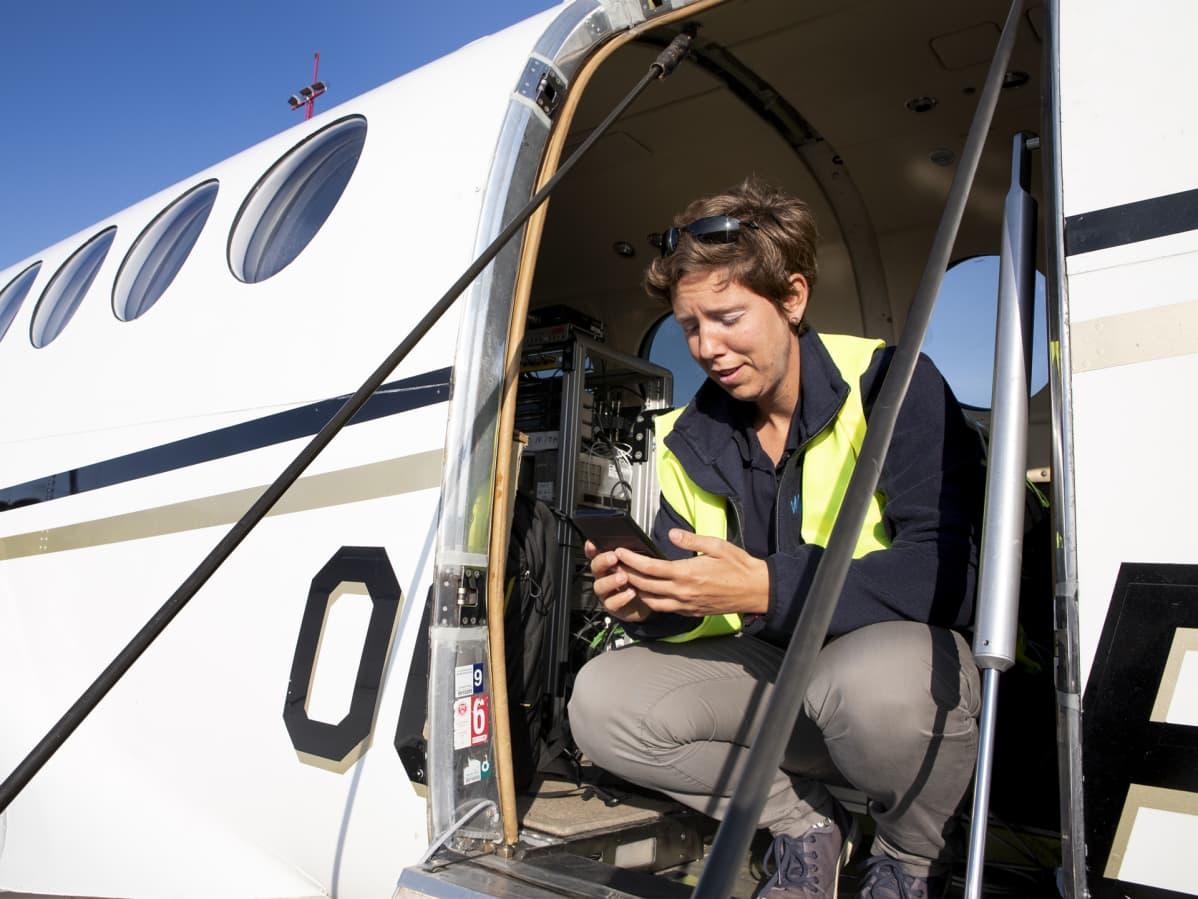 Lentokapteeni Anneleen Smits istuu lentokoneen oviaukossa.