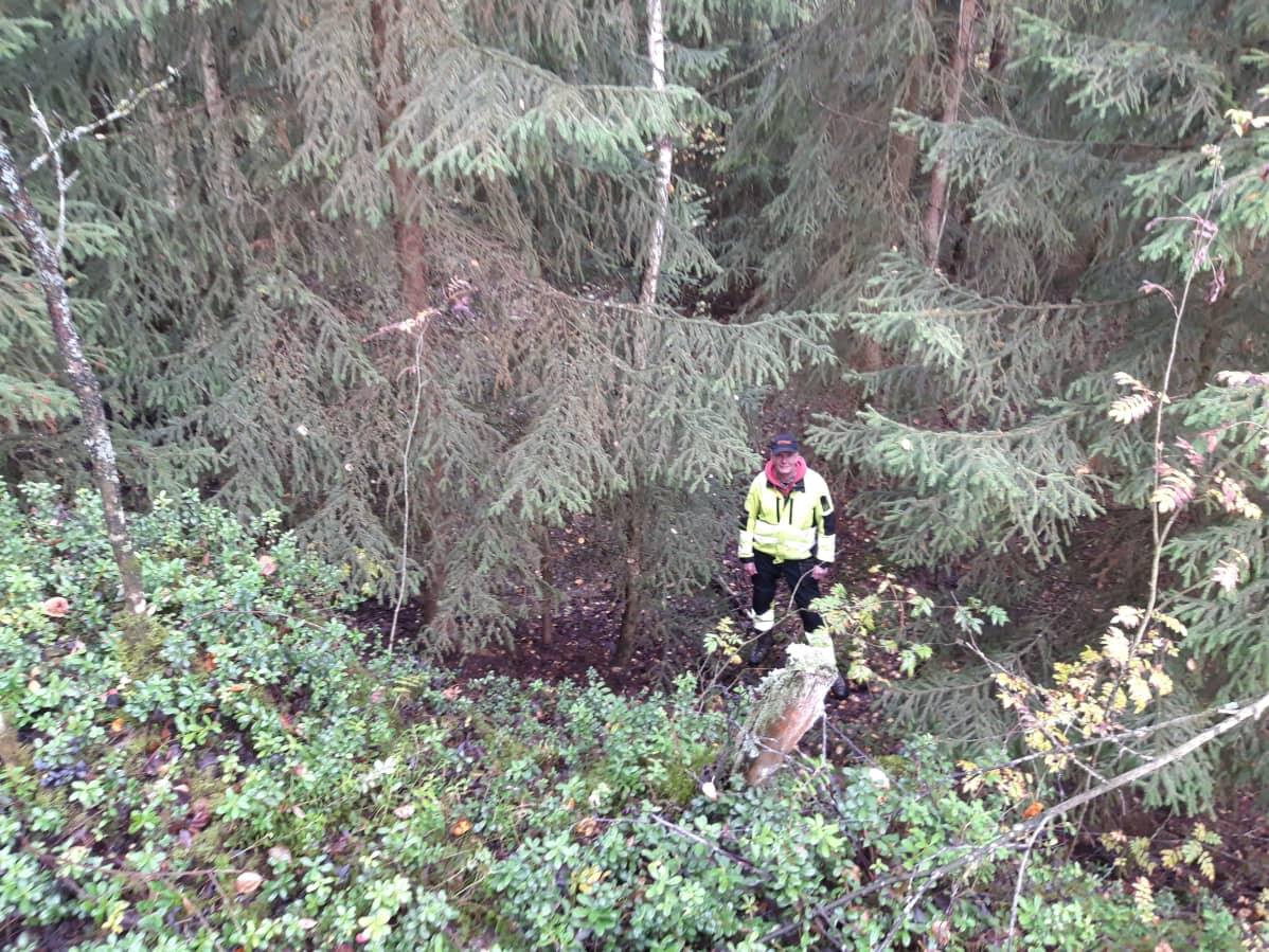 Pentti Risla seisoo metsässä.