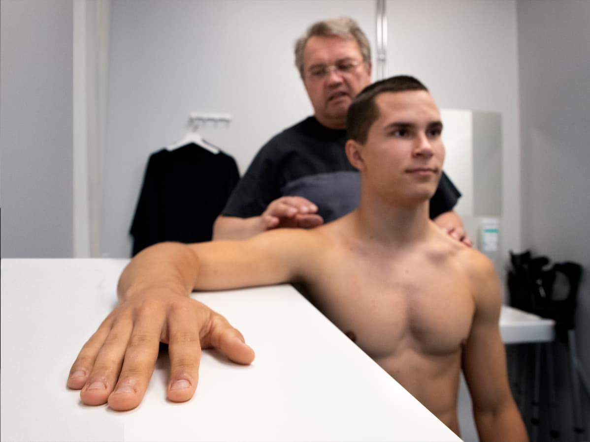 Urheilufysioterapeutti Peter Halén ohjaa vastaanotollana seiväshyppääjä Urho Kujanpäätä lepuuttamaan hartioita.