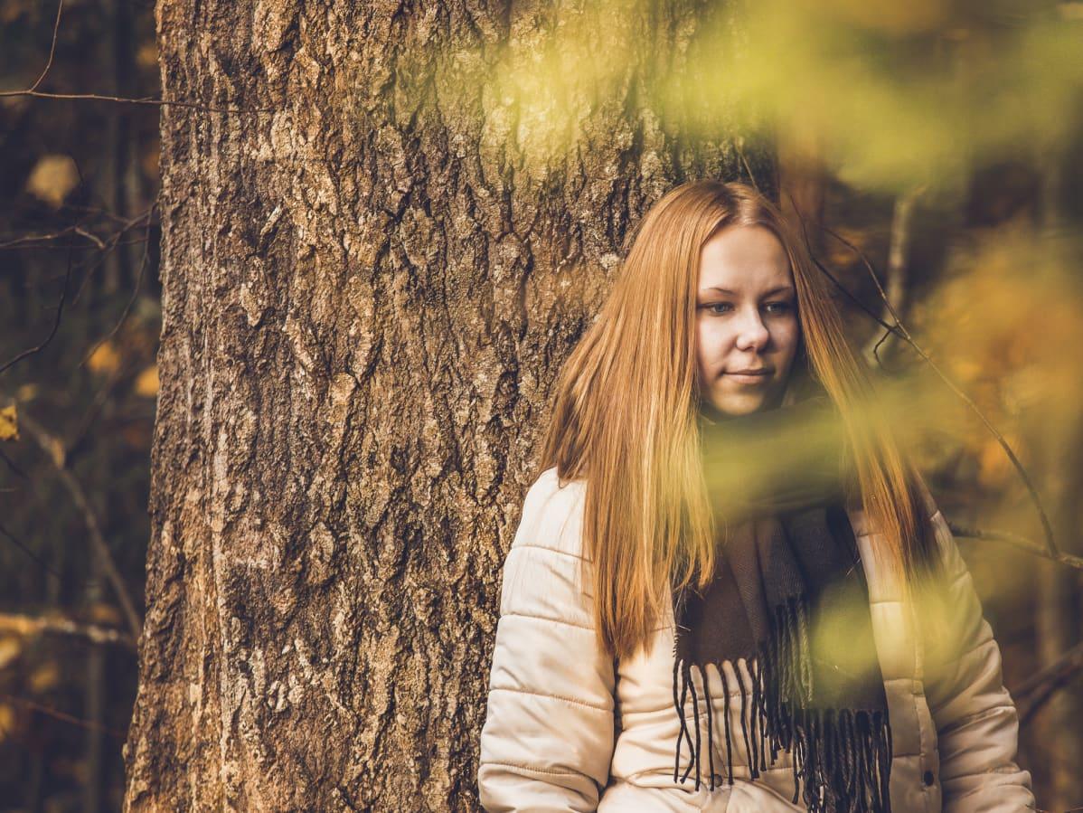 Nainen seisoo metsässä