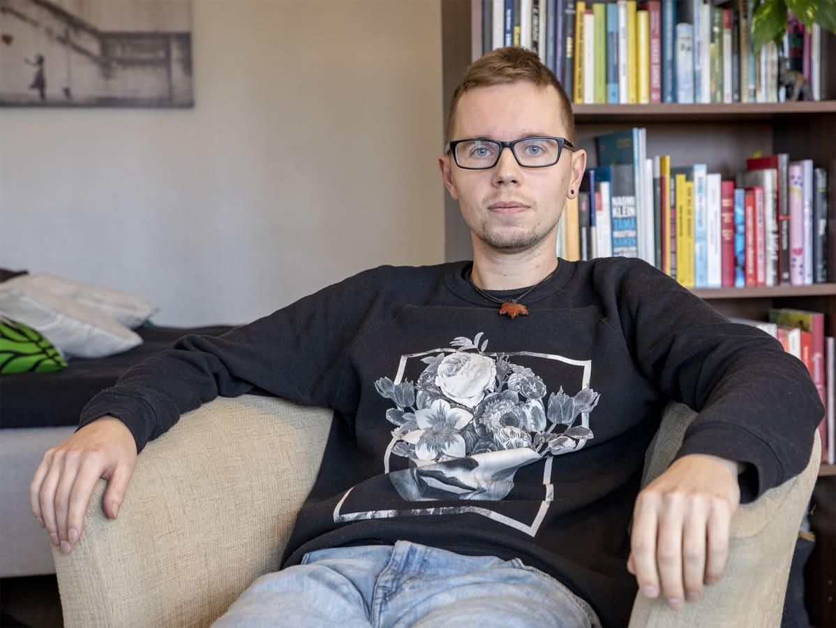 Kestävän hyvinvoinnin kokemusasiantuntija Mikko Valtonen istuu tuolilla kotonaan kirjahyllyn edessä.