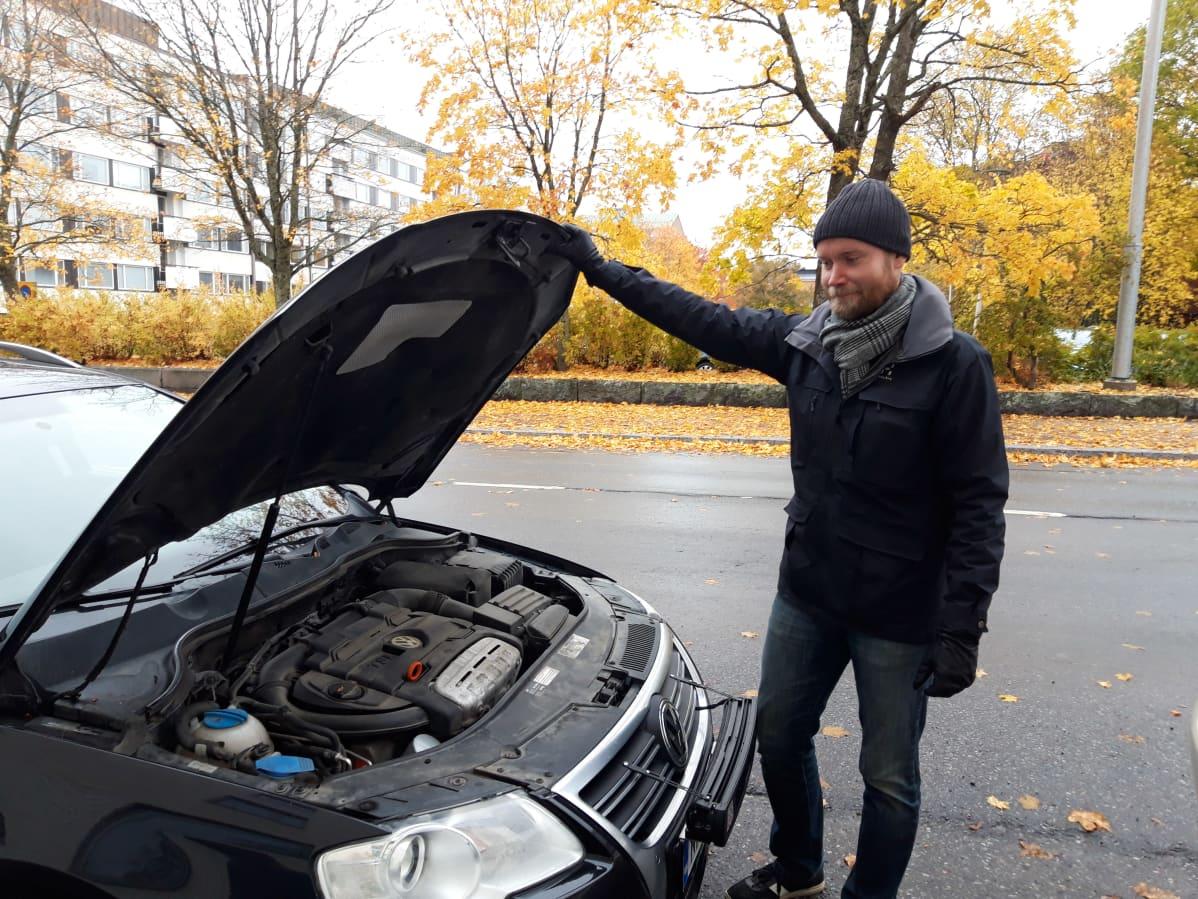 Mies avaa auton konepellin.