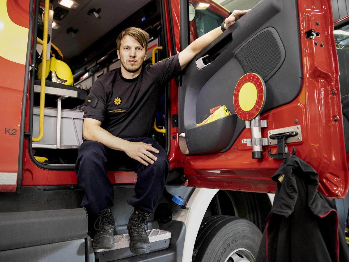 Palomies Pekka Kolehmainen istuu paloauton oviaukossa Äänekosken paloasemalla.