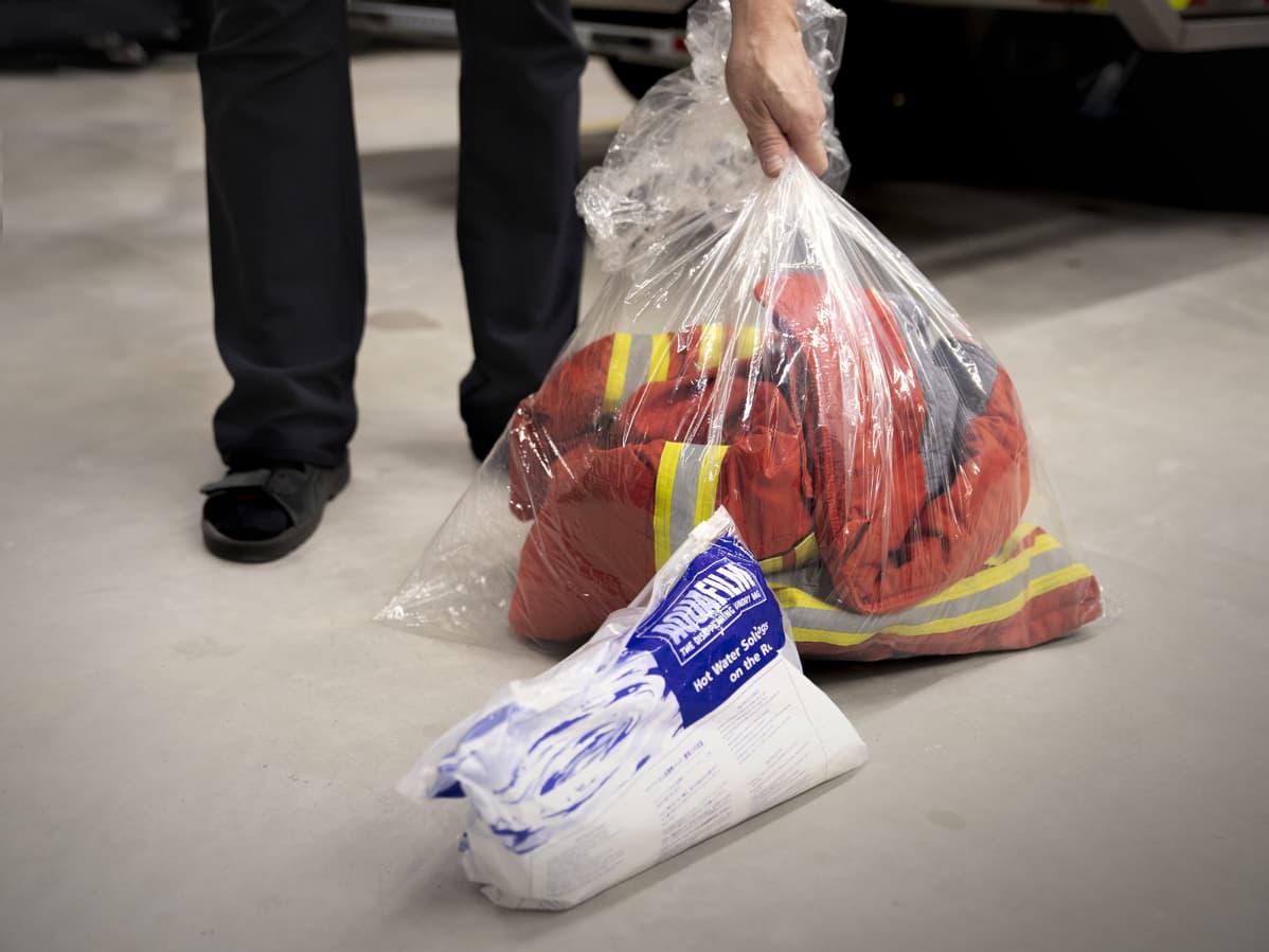 Palomiehen likainen sammutusasu itsestäänsulavassa pesupussissa.