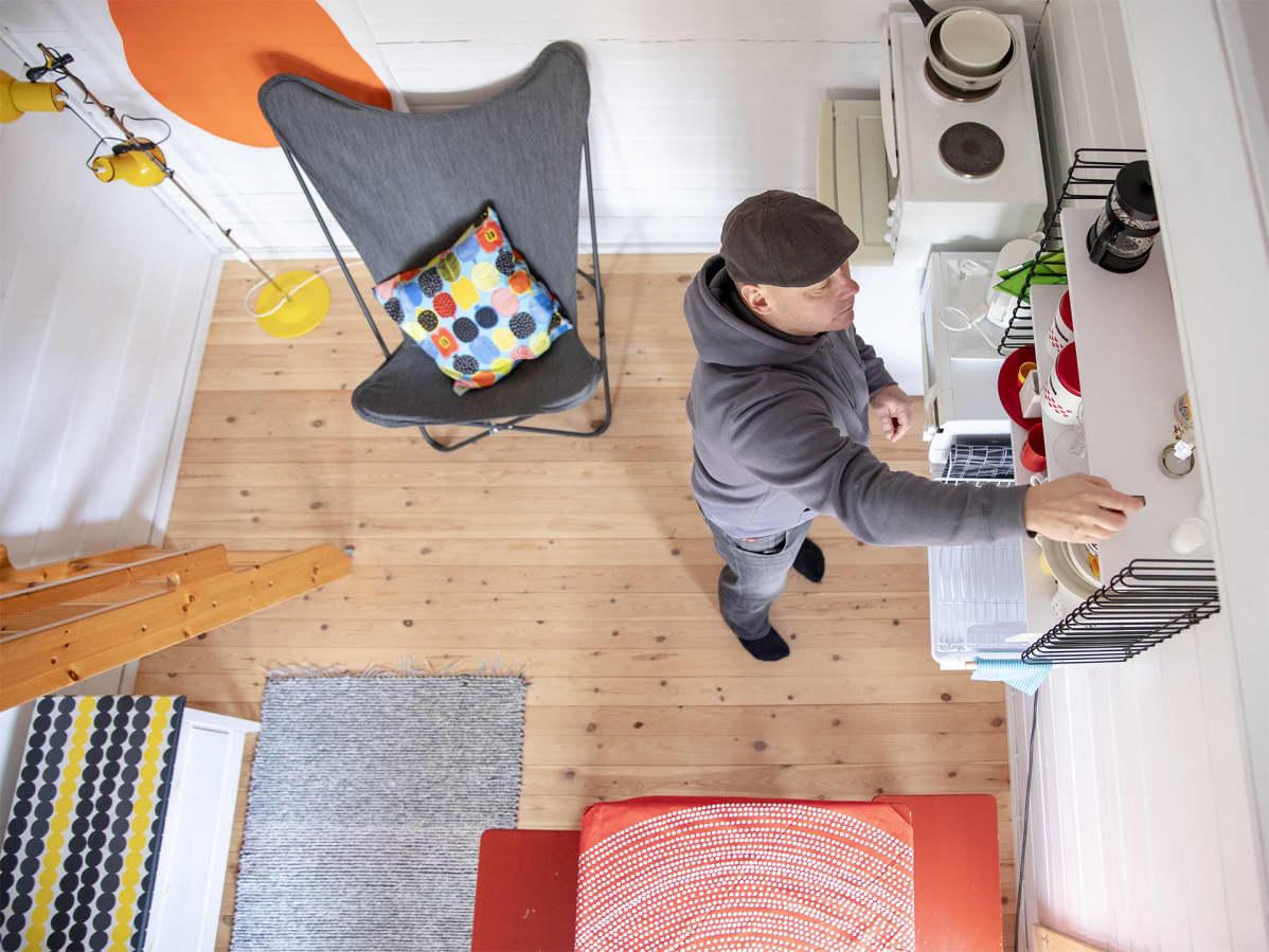 Sami Sällinen asettelee astioita mökin hyllyyn.