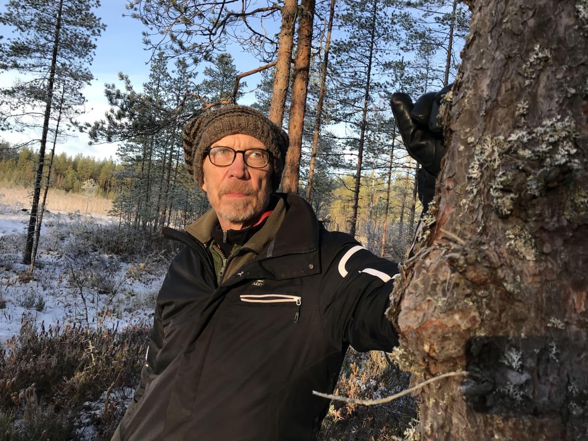 Luontokuvaaja Olli Korhonen nojaa puuhun.