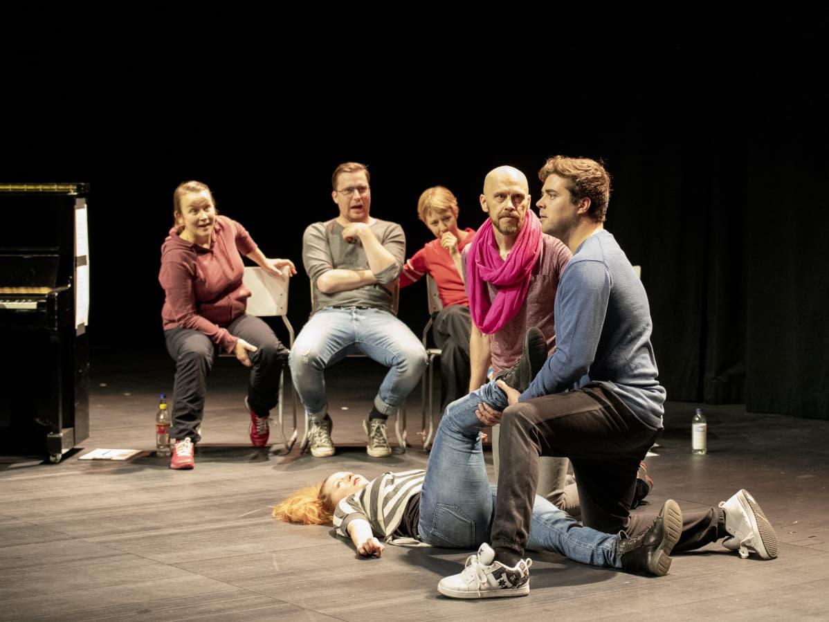 näyttelijä makaa lavalla jalka kohotetttuna, kaksi näyttelijää pitelee hänen jalkaansa