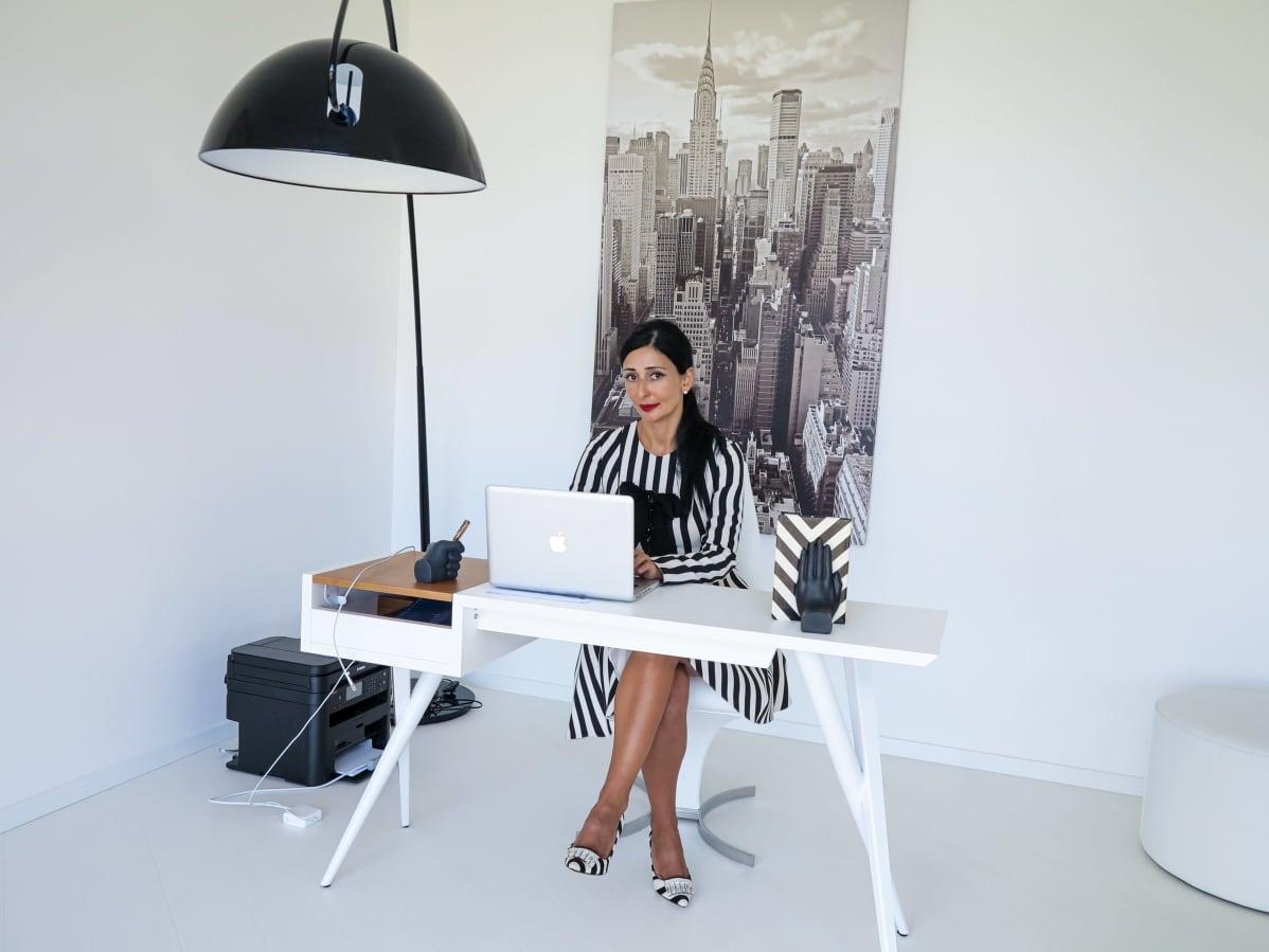 Tyylikäs nainen istuu toimistollaan.