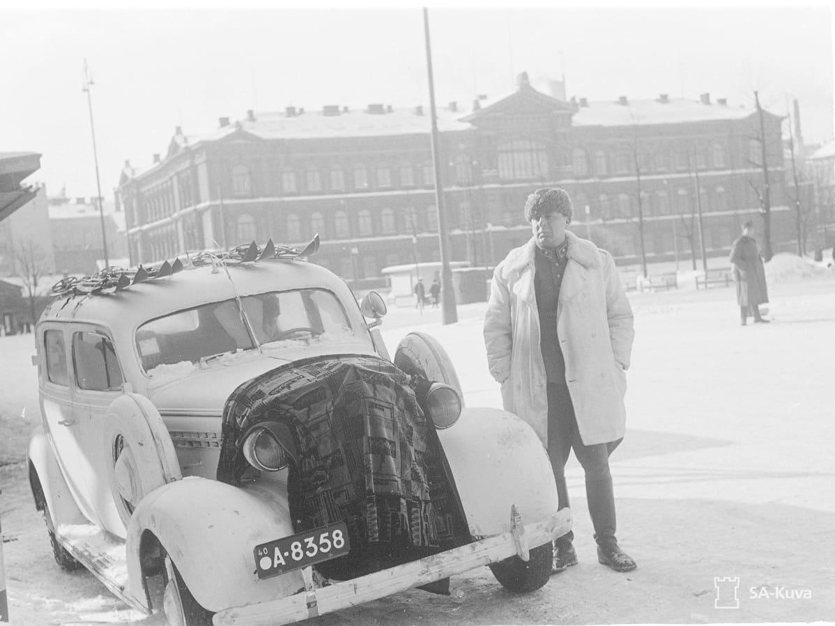 Reino Hallamaa seisoo auton vieressä talvisissa sotilasvaatteissa.
