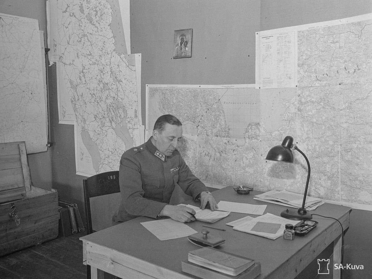 Reino Hallamaa tutkiskelee papereita työpöydän äärellä vanhassa sota-ajan valokuvassa.