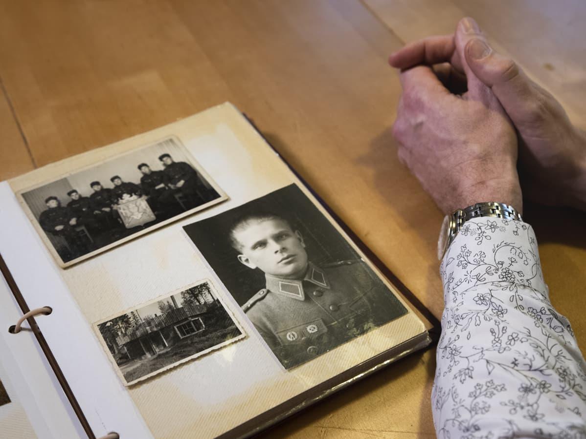 Valokuva-albumissa kuvia Aimo Koivusesta, vieressä Mika Koivusen kädet.