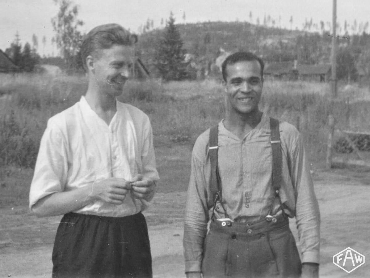 Holger Sonntag hymyilee siviilivaatteissa, vieressä toinen mies joka katsoo Sonntagia.