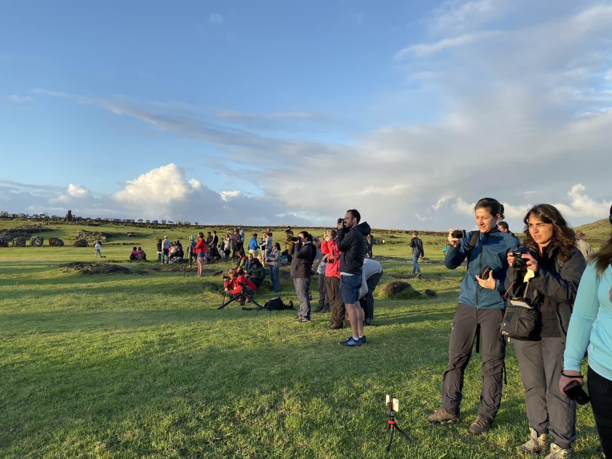 Turisteja kameroineen odottamassa auringonnousua Ahu Tongarikin moai-patsailla.