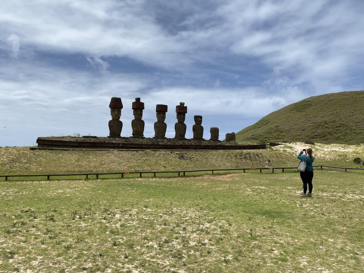 Turisti ottaa kuvaa seitsemästä vierekkäin seisovasta kivipatsaasta.