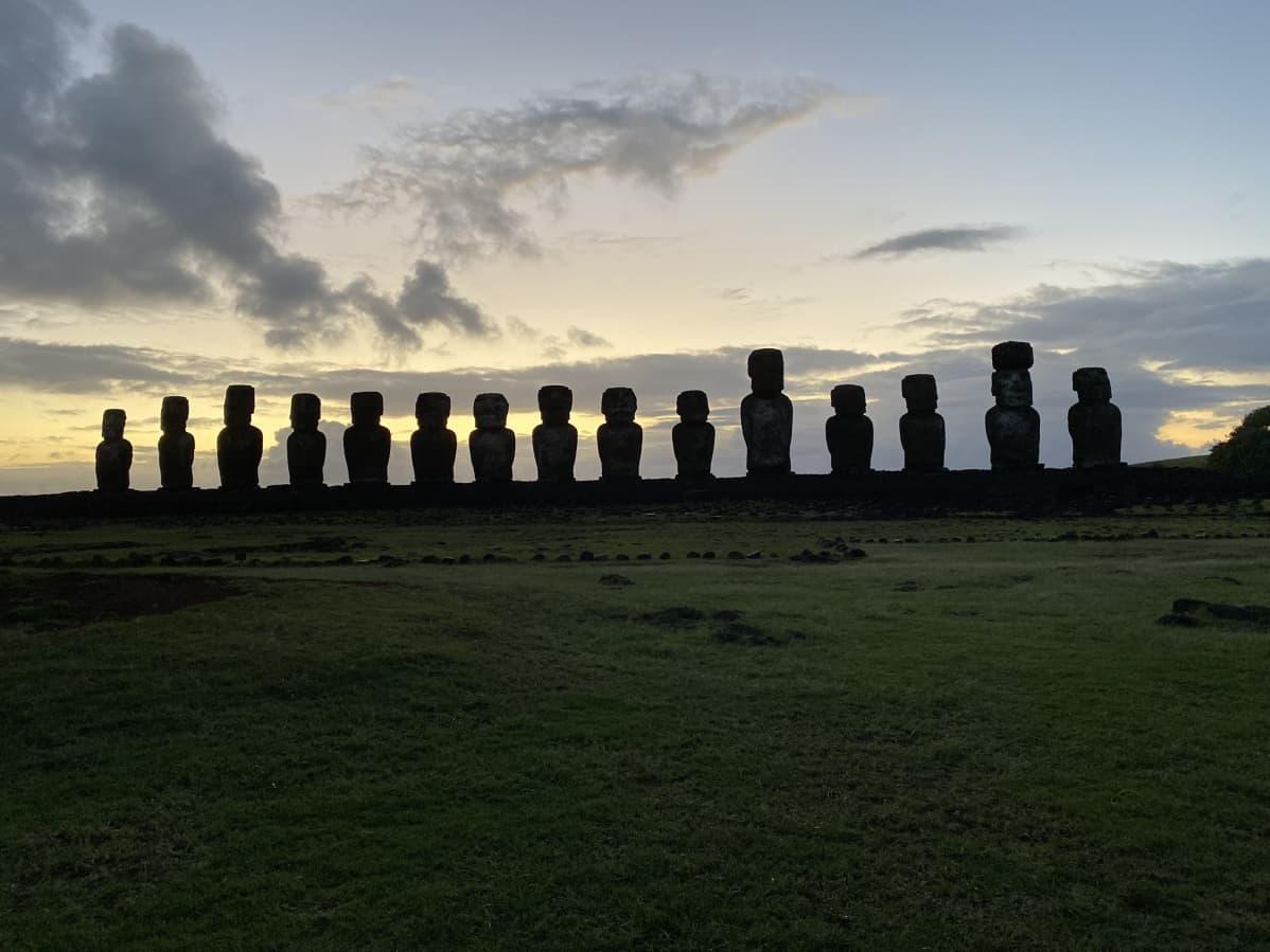 15 kivipatsaan tummat siluetit auringonnousua vasten