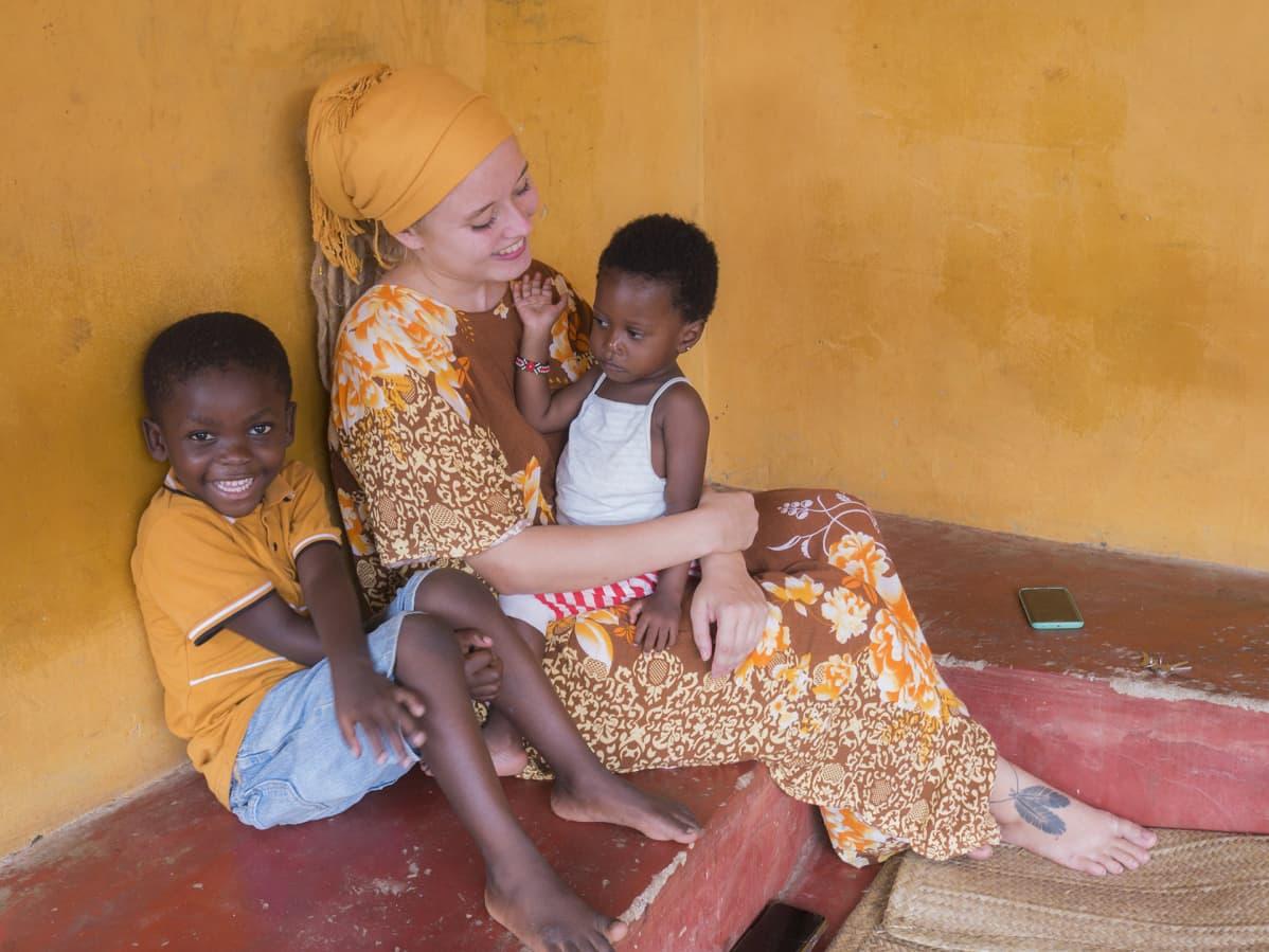 Nainen istuu lasten kanssa talon lattialla.